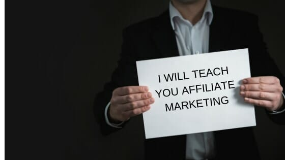 man holding sign that saysi will teach you affiliate marketing